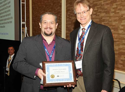 Ted Hartwig of CSA presents the Award Plaque to Philippe Masson. (Photo taken at ASC2010)